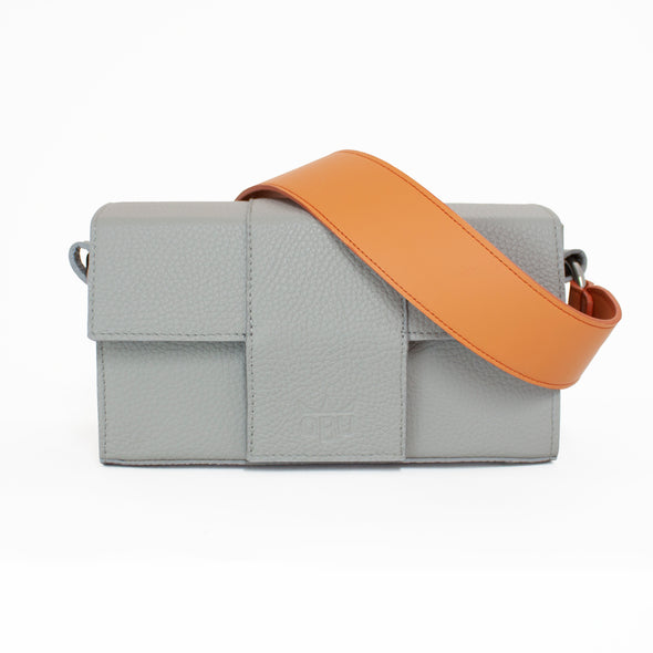 Light grey handbag with orange strap. Interesting cuboid design. Perfect for your camera. Designed in Ireland and made in Scotland from Italian sustainable leather.