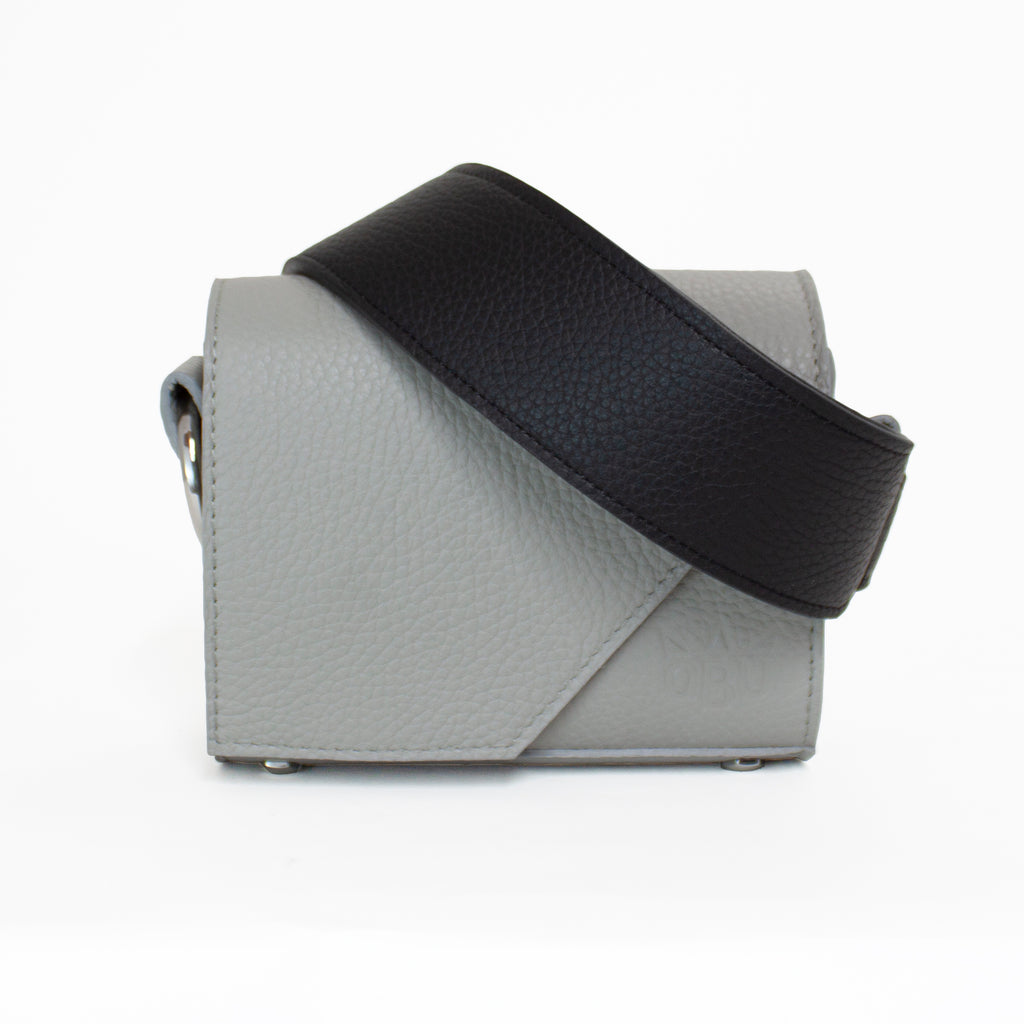 New luxury accessories brand QBU's aOma handbag in grey contrasted with a black strap. Great bag for everyday and special occasions.