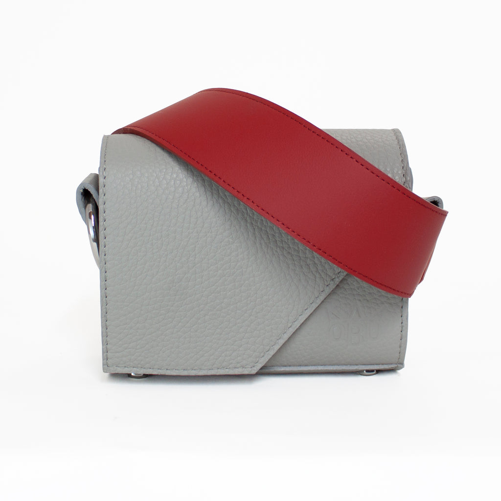 This grey small crossover bag with a gorgeous red strap is perfect for any occasion. Italian leather, Irish linen lining and all other European materials.