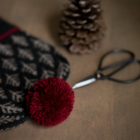 knit hat with red pom pom on a table with scissors and a pinecone