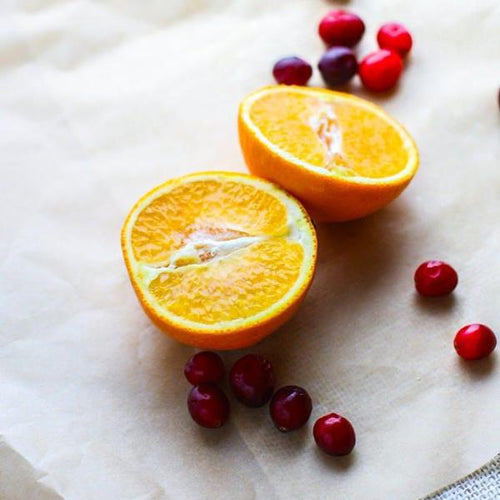a freshly sliced orange along side a bunch of fresh cranberries
