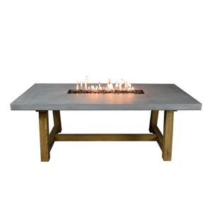 Large concrete dining table with wooden legs and a fire pit in the center