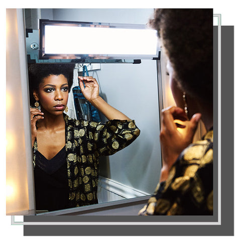 Woman checking her reflection in mirror with Eyelight