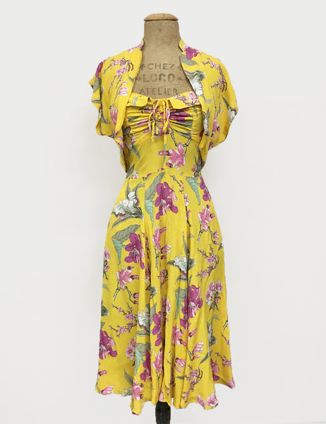 500 Vintage Style Dresses for Sale | Vintage Inspired Dresses Yellow & Purple Iris Floral 1940s Inspired Marta Halter Swing Dress $178.00 AT vintagedancer.com
