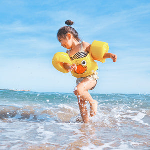 Little kid with swimming aids splashing on a wavy beach on a sunny day in the water.