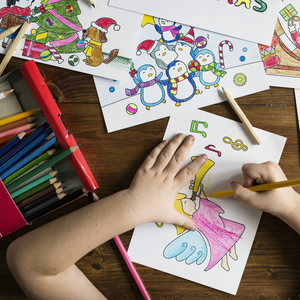Picture of little hands using coloured pencils to colour a picture on the table filled with other colourful drawings.
