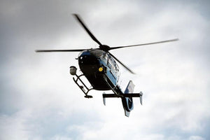Blue and silver police helicopter flying above Wall Mural Wallpaper - Canvas Art Rocks - 1