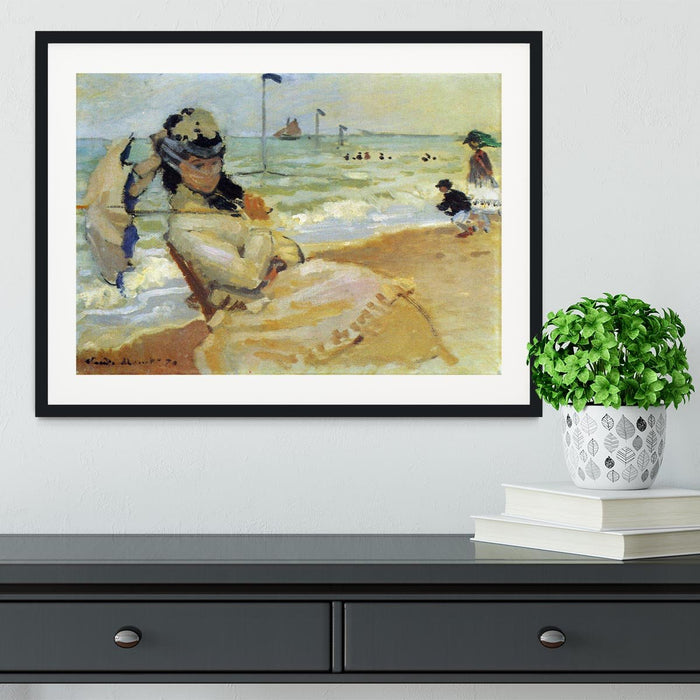 Camille on the beach at Trouville by Monet Framed Print