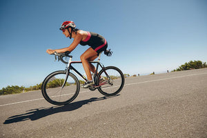 Female cyclist on a country road Wall Mural Wallpaper - Canvas Art Rocks - 1