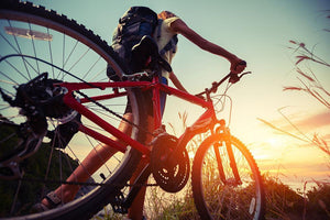Hiker with bicycle watching sunset Wall Mural Wallpaper - Canvas Art Rocks - 1