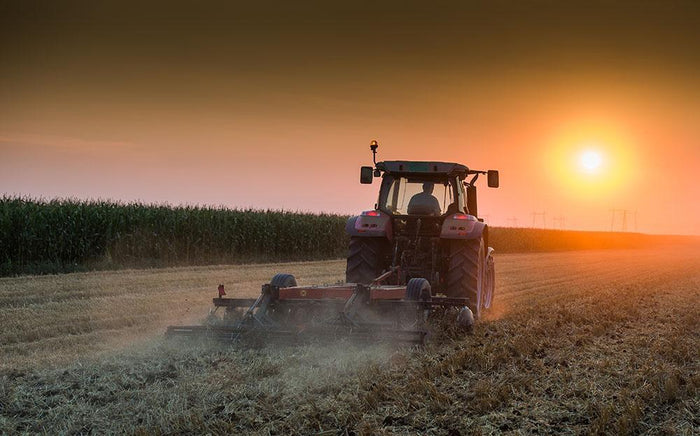 Tractor plowing field at dusk Wall Mural Wallpaper