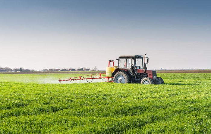 Tractor spraying wheat field Wall Mural Wallpaper