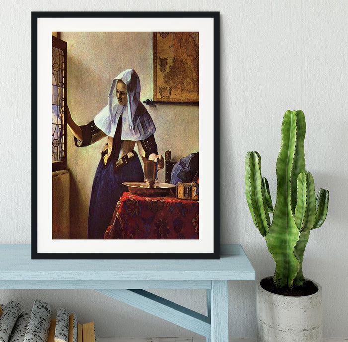 Young woman with a water jug at the window by Vermeer Framed Print