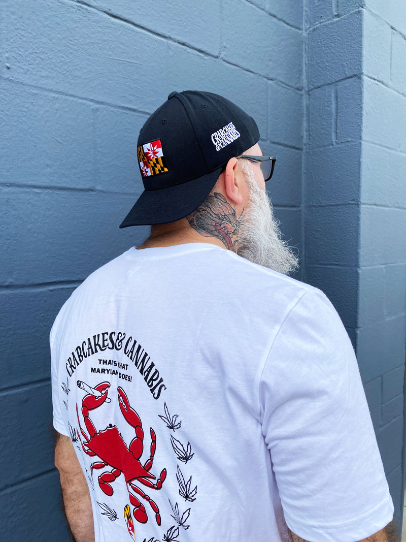 Man wearing black crabcakes and cannabis snapback and white crab emblem tee shirt, standing on a grey wall.