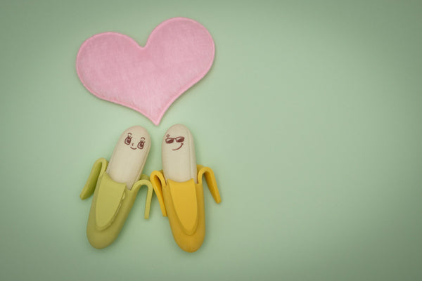2 Bananas in love, green background, pink love heart
