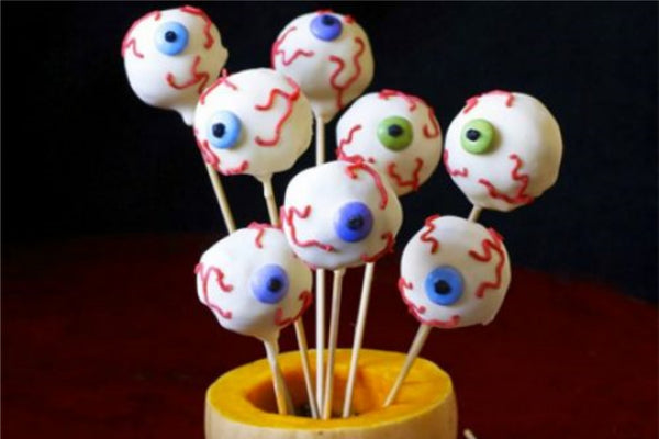 Halloween cake pops shaped as gruesome eyeballs. Featured on dark red background