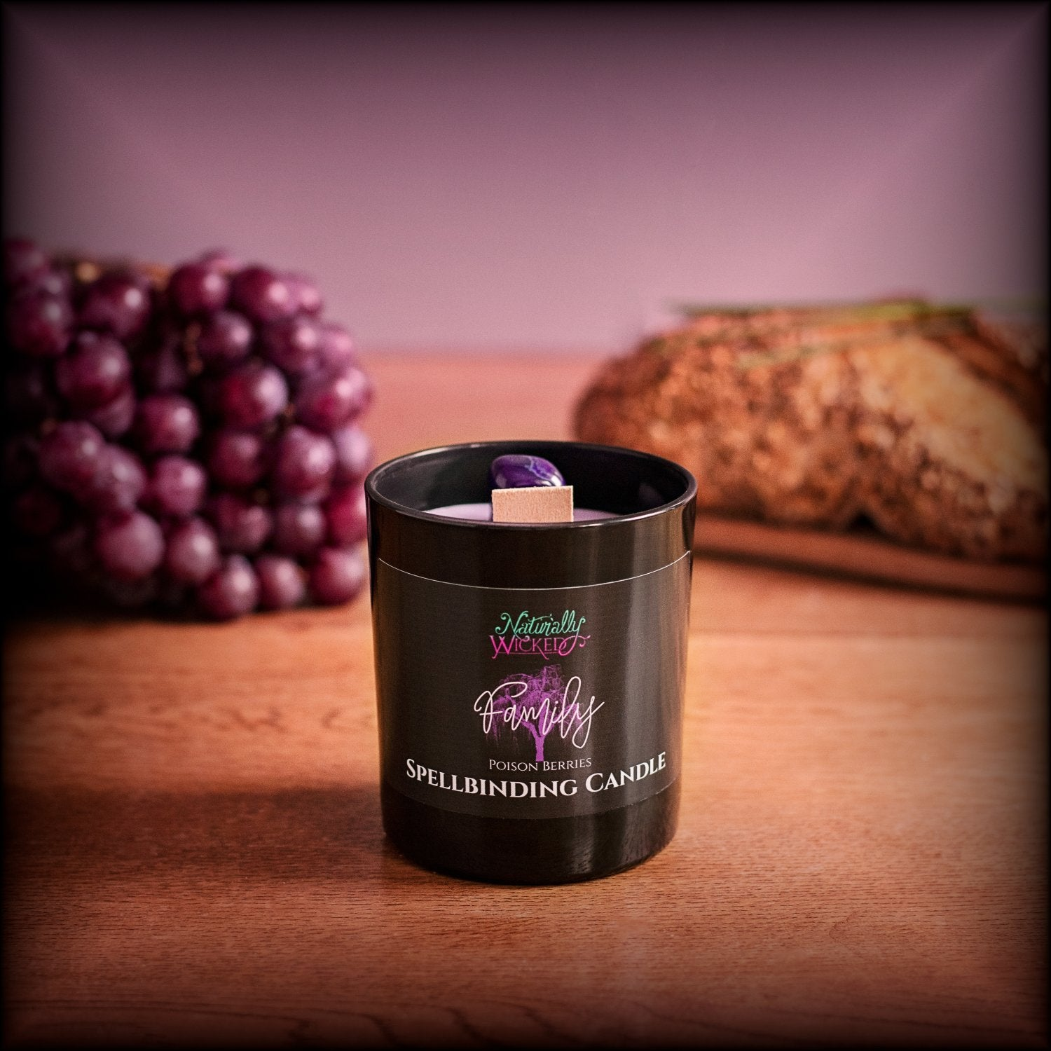 Naturally Wicked Spellbinding Family Candle With Bright Purple Crystal Sits In Front Of Purple Grapes & Home Cooked Bread