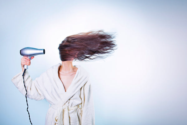 Lady drying long dark brown hair with hair dryer