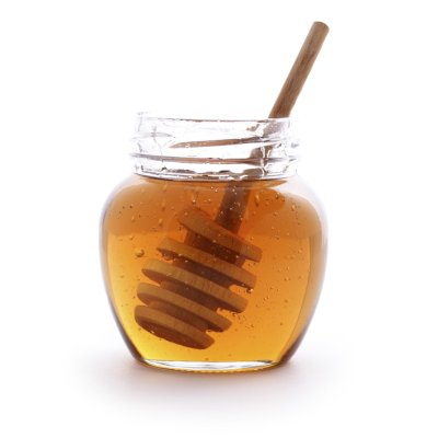 A Clear Jug Full Of Thick Golden Honey & A Honey Stirrer