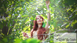Naturally Wicked Redheaded Woman Picking Leaves In Green Forest With Loved By Celebs Logo