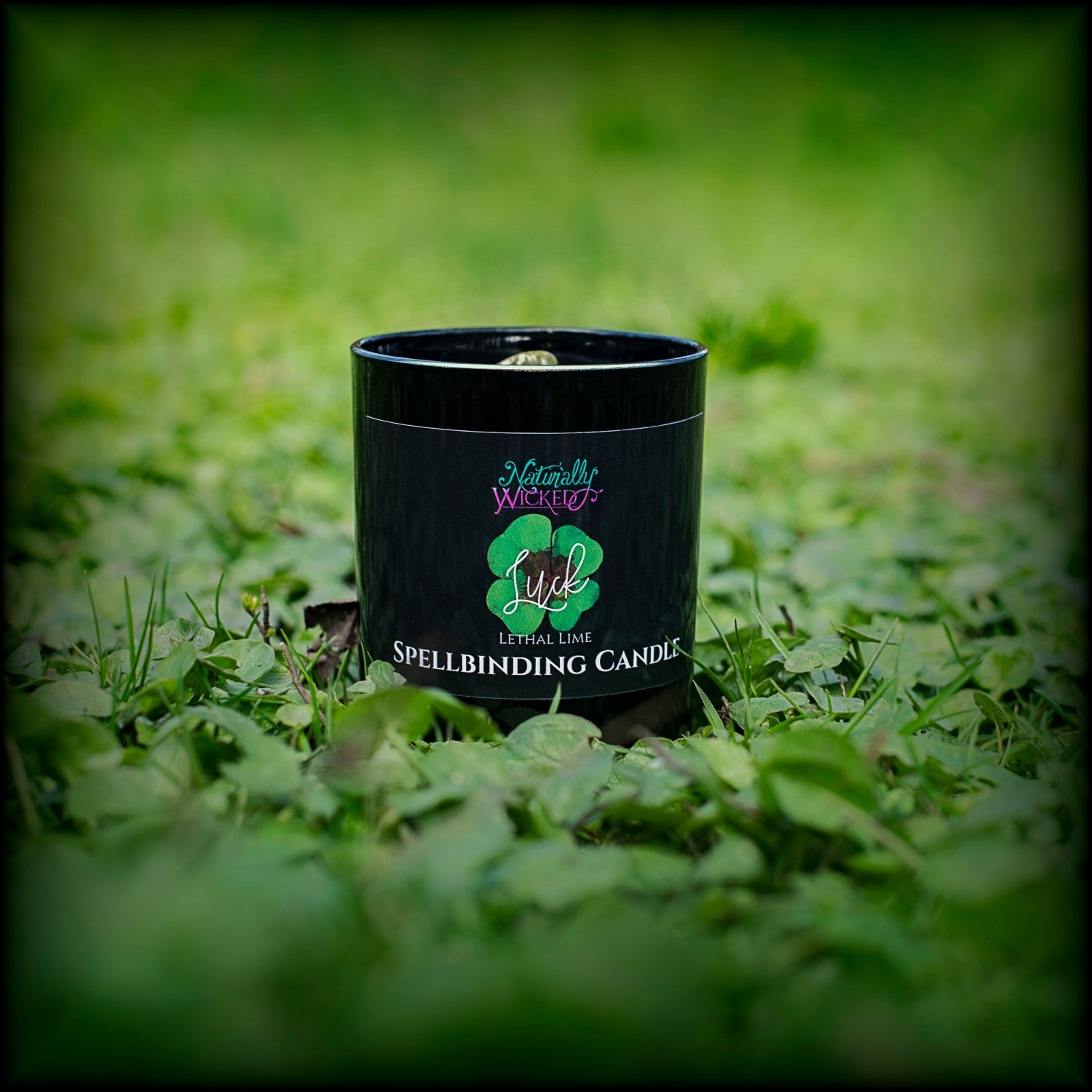 Naturally Wicked Spellbinding Luck Candle Entombed With Green Spotted Epidote Crystal Sits in Bright Green Clover Field