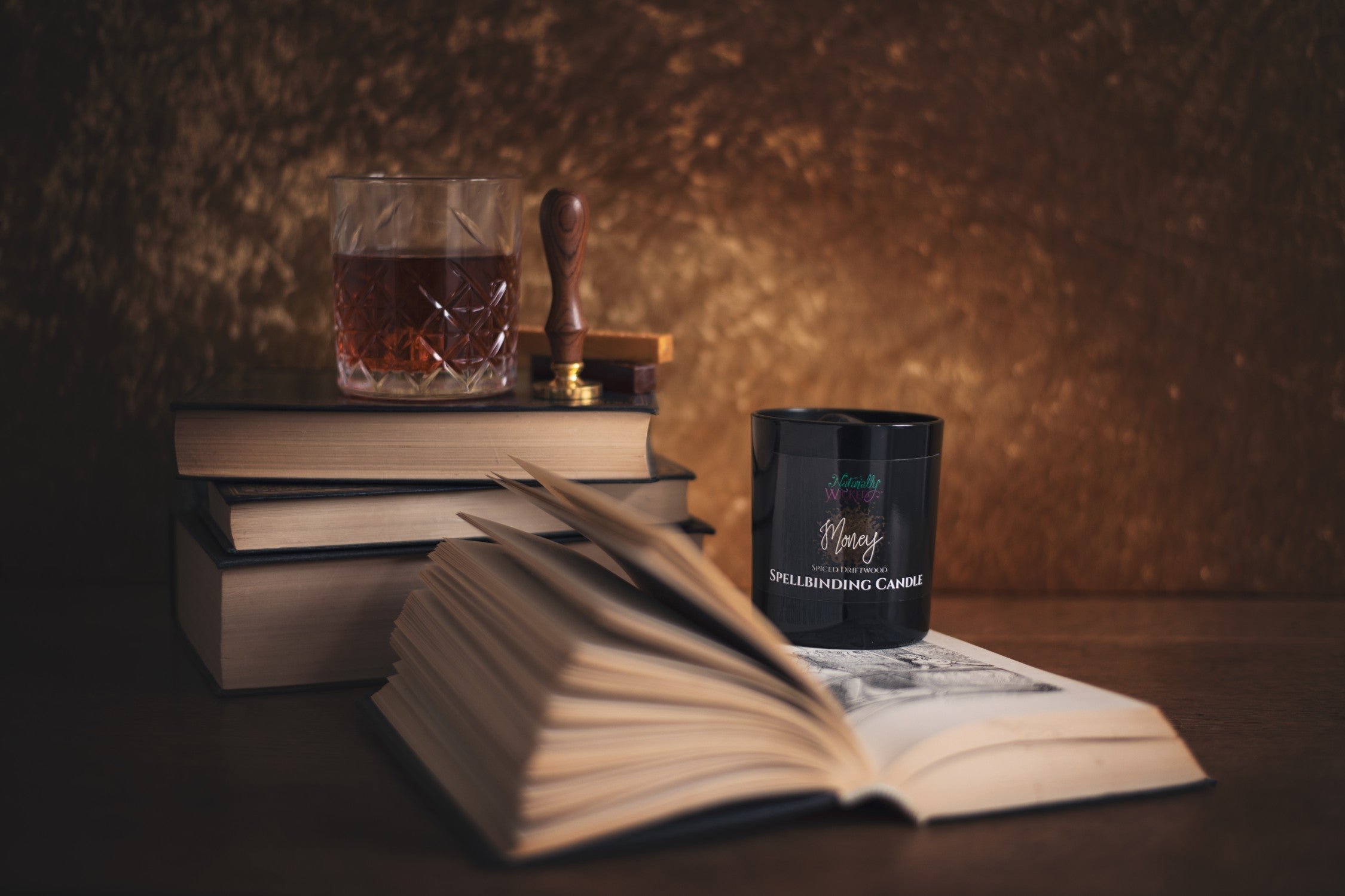 Naturally Wicked Spellbinding Money Candle On Top Of Sophisticated Book With Whiskey In Background
