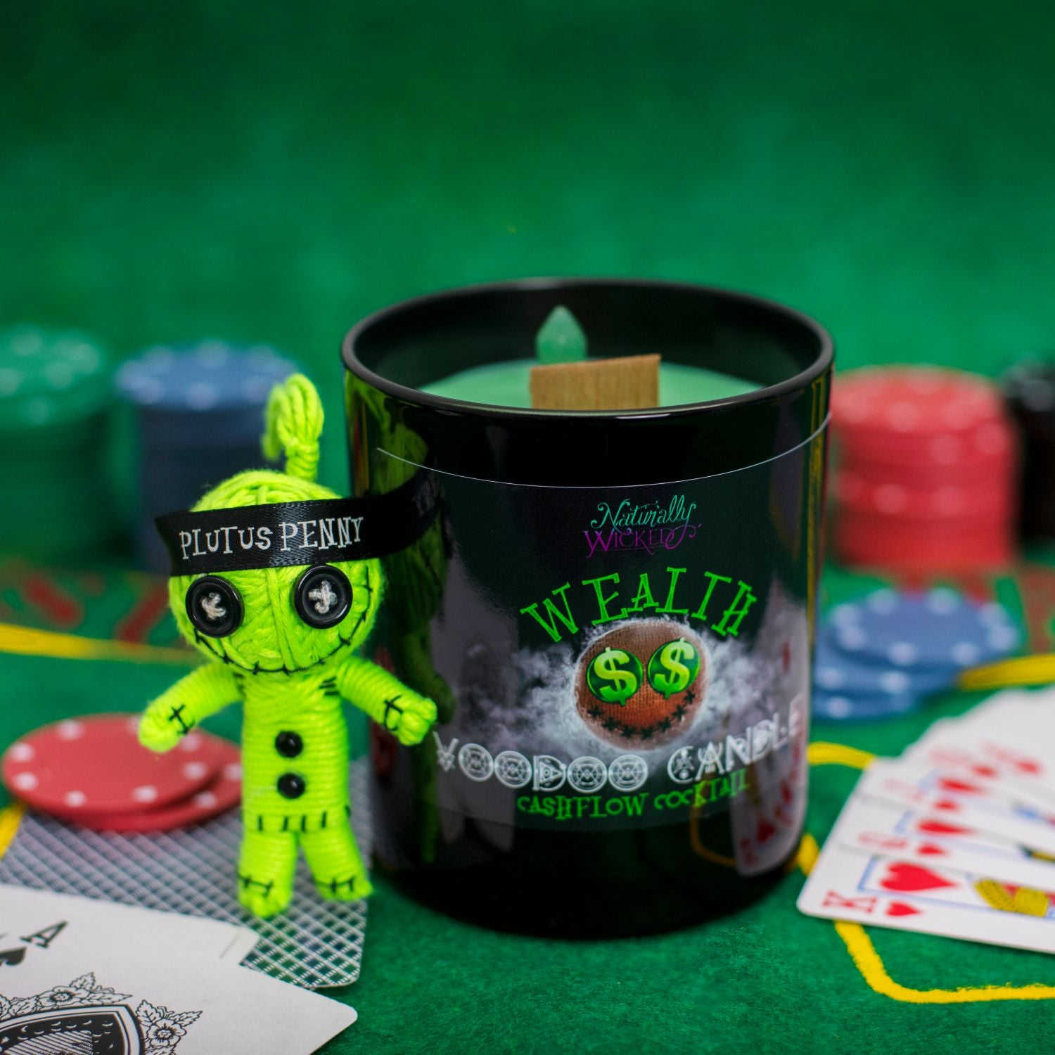 Naturally Wicked Voodoo Wealth Candle On Green Casino Table Amongst Green Voodoo Doll, Poker Chips & Playing Cards