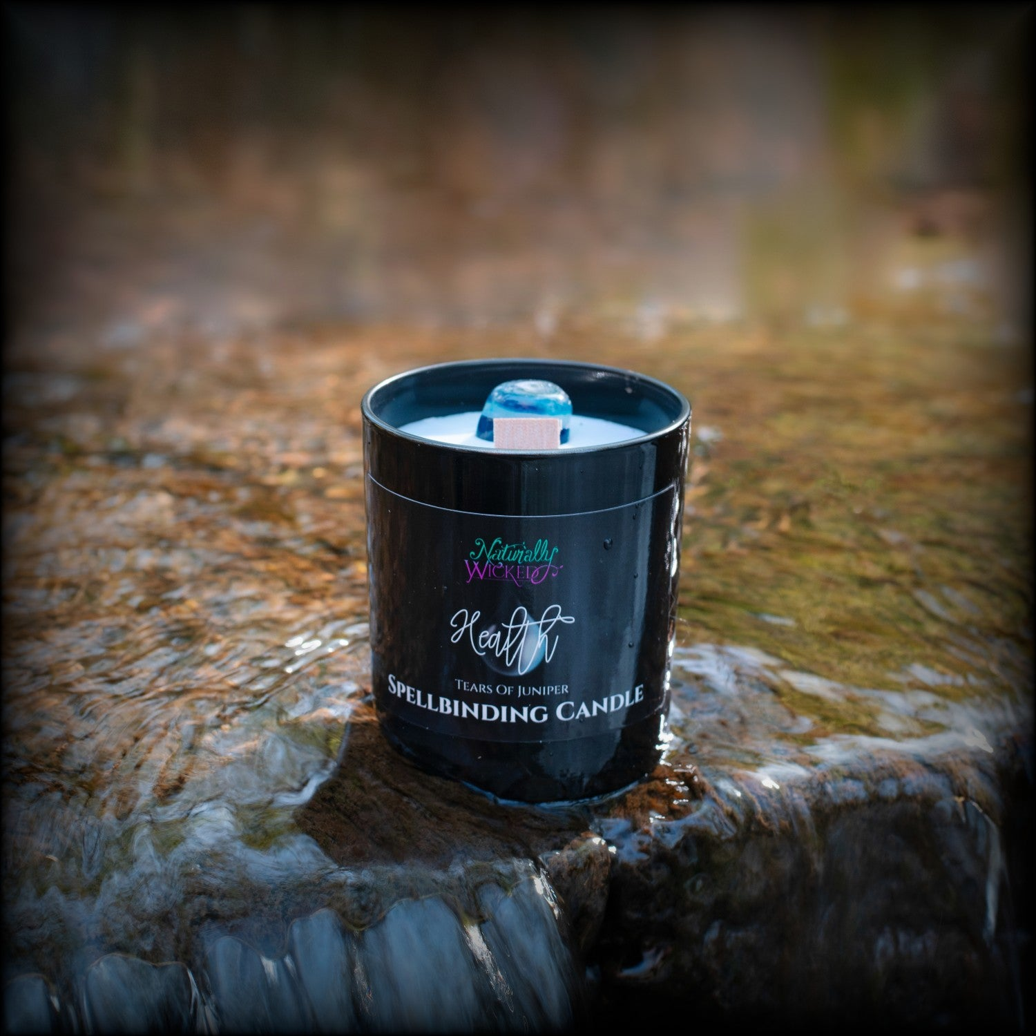 Naturally Wicked Spellbinding Health Candle With Bright Blue Crystal Resides In Clear Flowing Water