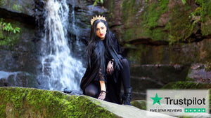 Naturally Wicked Queen Dressed Black On Green Natural Background With Waterfall - Trustpilot Logo In Corner