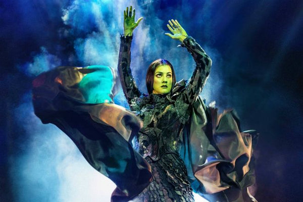 Wicked witch with green face and blue smoke background