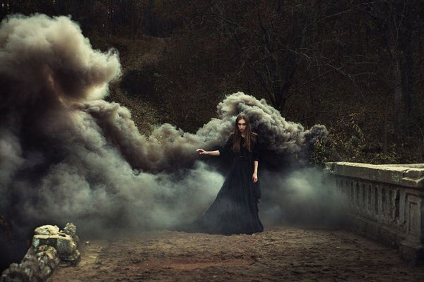 Witch performing witchcraft grey smoke background