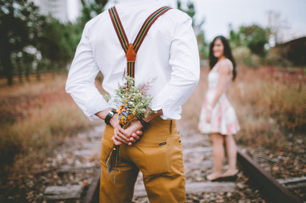 Gentleman giving lady suprise flowers