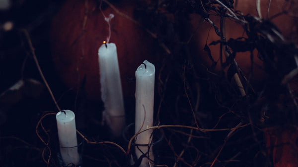 White spooky candles on black background