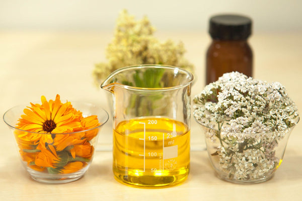 Jojoba Oil in glass beaker, flowers in the background.