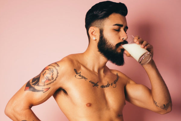 Dark haired man drinking milk topless