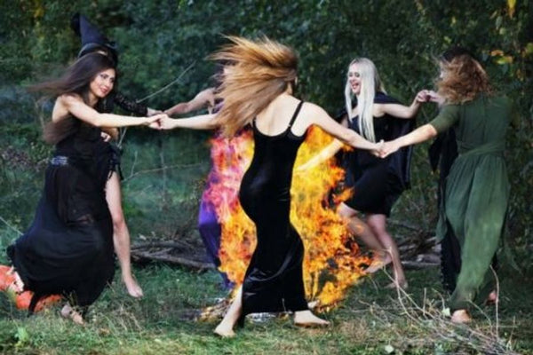 ladies dancing around the campfire like witches in nature
