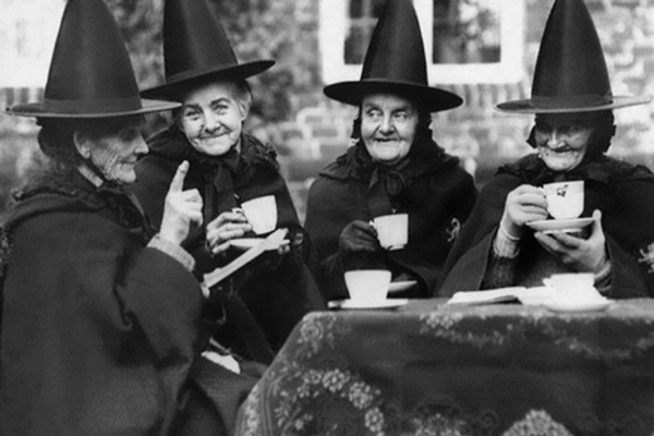 4 lady witches drinking tea outdoors image in black and white