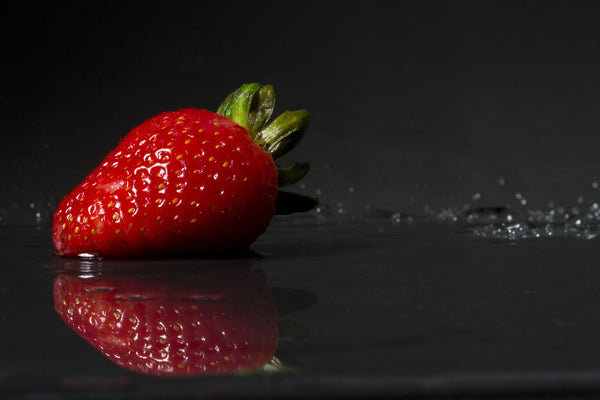 Strawberry slashing in water on dark background