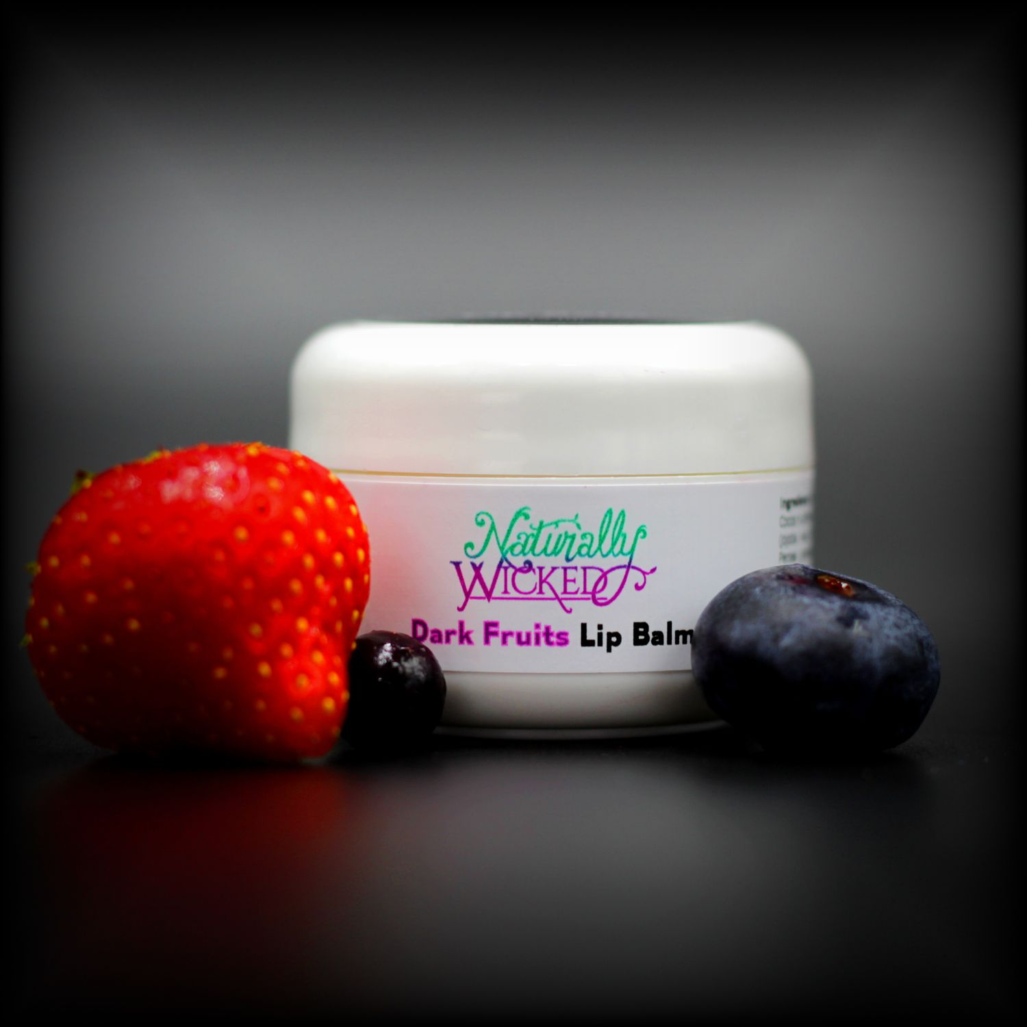 Naturally Wicked Dark Fruits Moisturising Lip Balm Surrounded By Strawberry, Blueberry & Blackcurrant