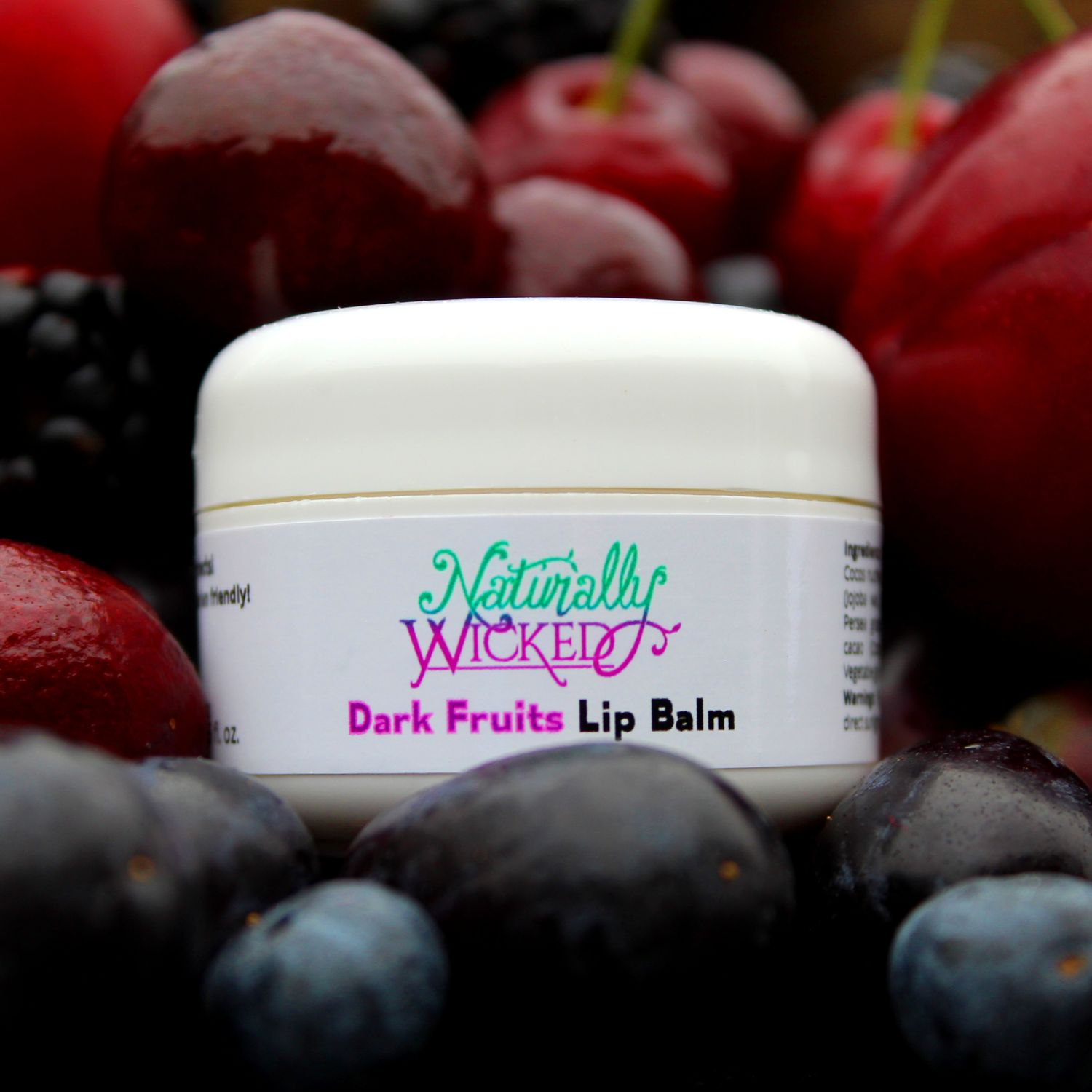 Naturally Wicked Dark Fruits Lip Balm Surrounded By Dark Plums, Blueberries, Blackberries, Cherries & Dark Grapes