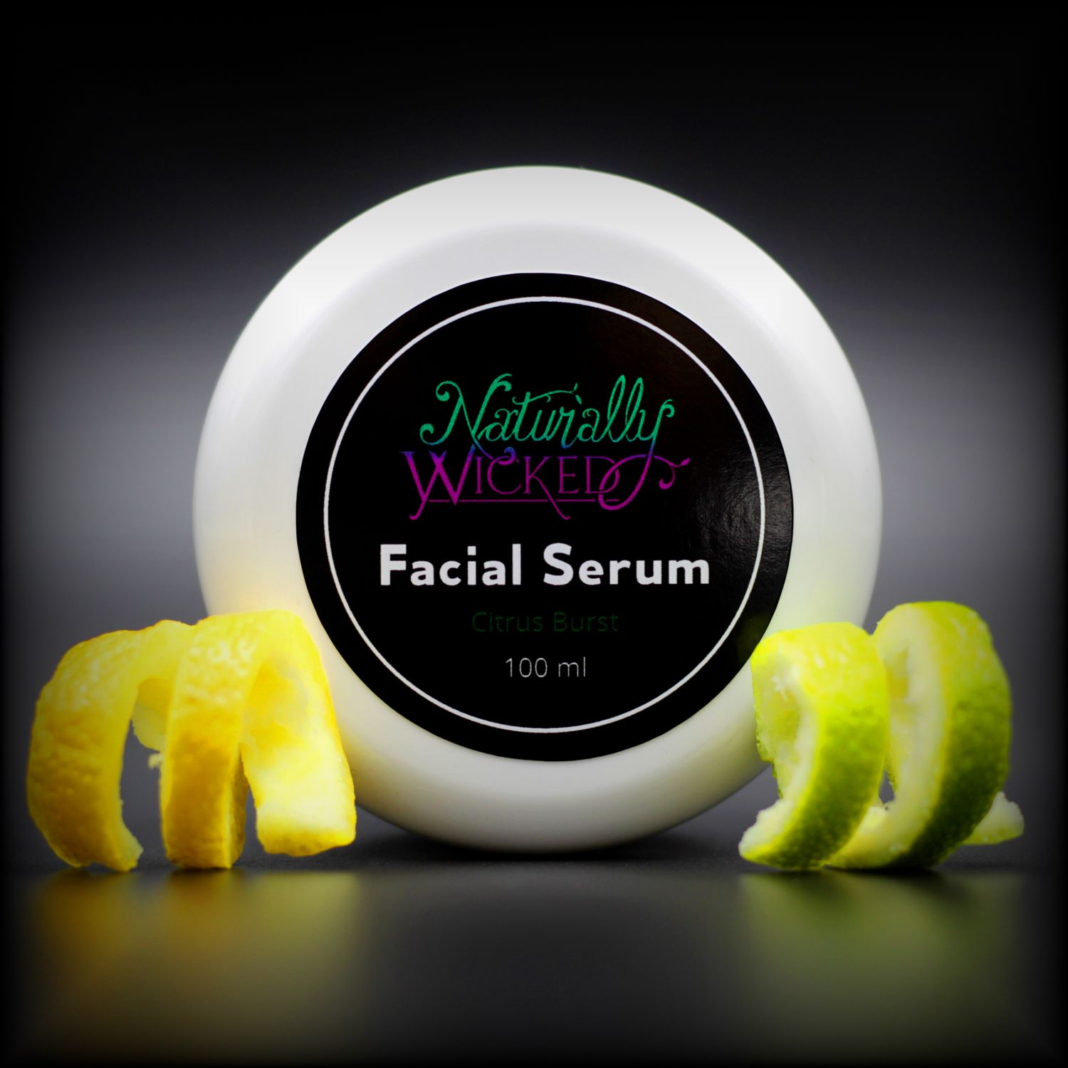 Naturally Wicked Citrus Burst Facial Serum Lid Surrounded By Sliced Yellow Lemon Twist & Sliced Green Lime Twist