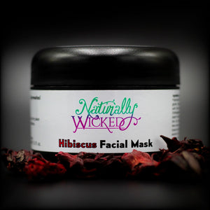 Naturally Wicked Hibiscus Facial Mask Surrounded By Bright Red Firming Hibiscus Flowers