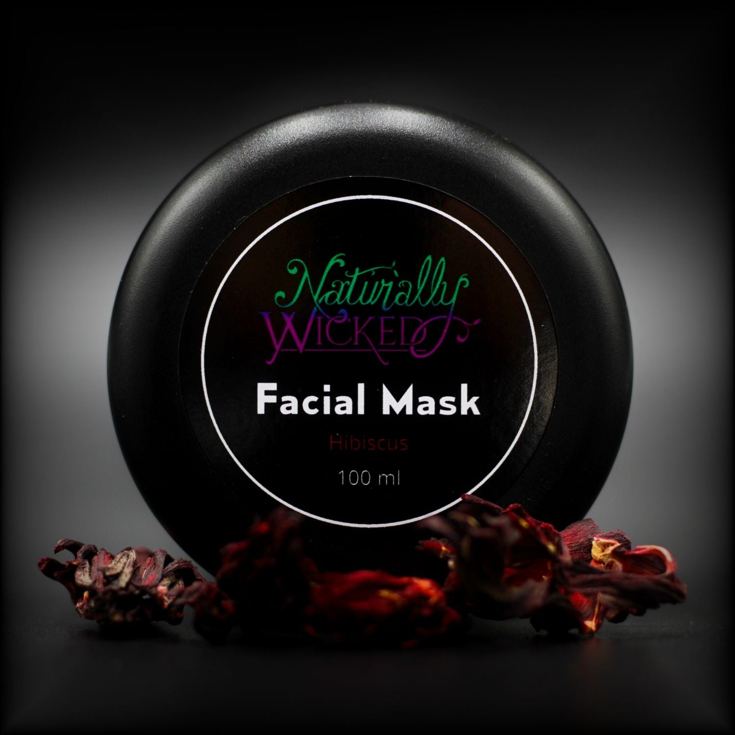 Naturally Wicked Hibiscus Facial Mask Lid Surrounded By Red Hibiscus Fllowers