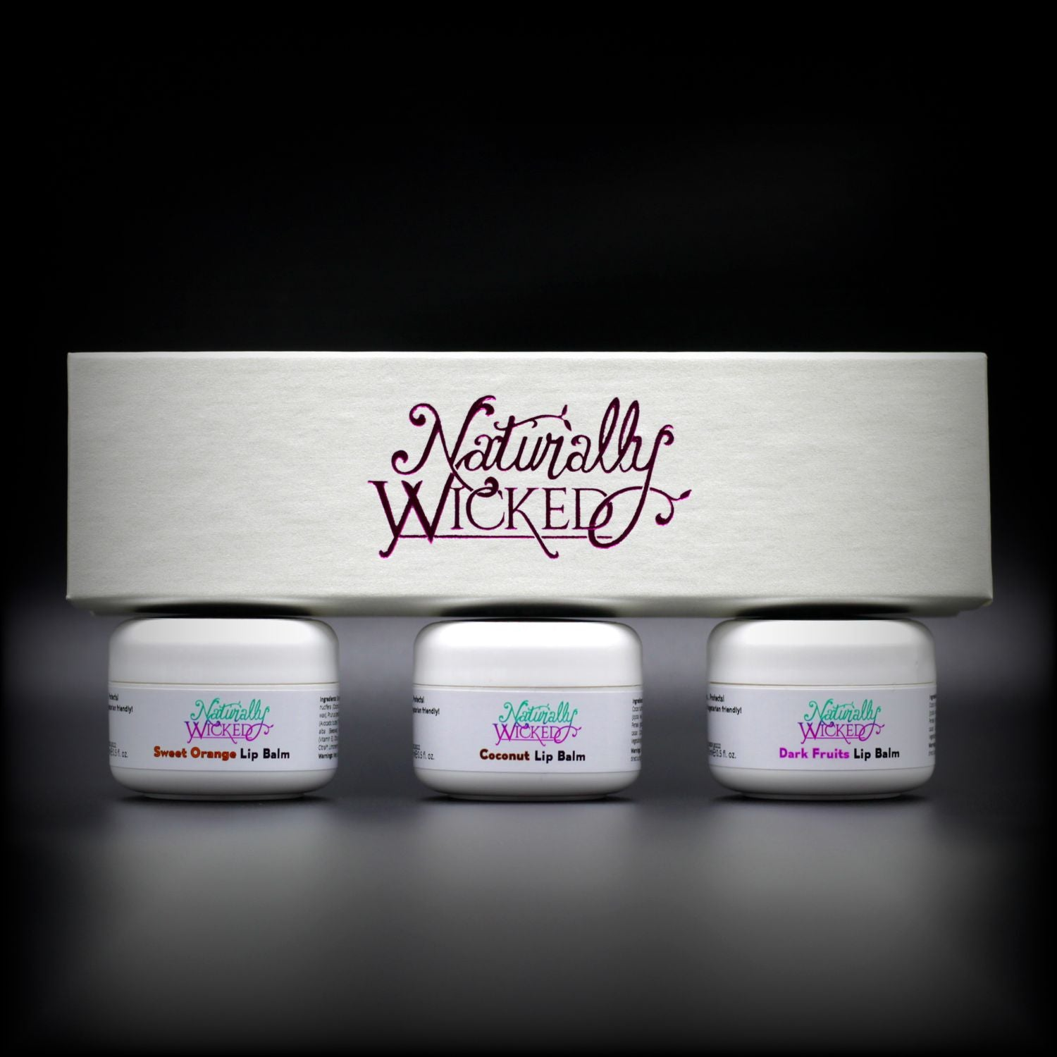Naturally Wicked Lip Balm Trio Box On Top Of 3 Luxury Fruit Filled White Lip Balm Containers; Coconut, Dark Fruits & Sweet Orange