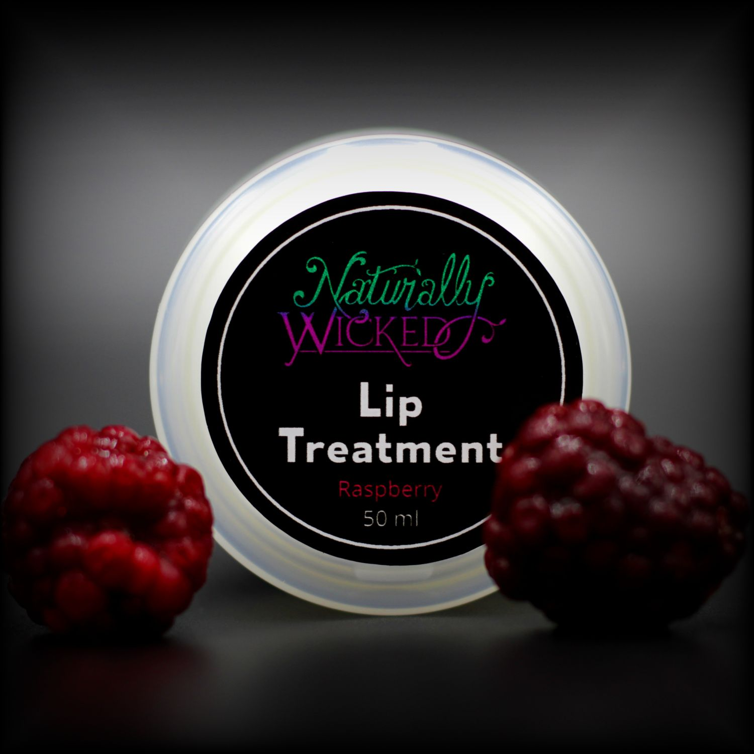 Naturally Wicked Raspberry Lip Treatment Lid With Two Bright Red Raspberries In Front