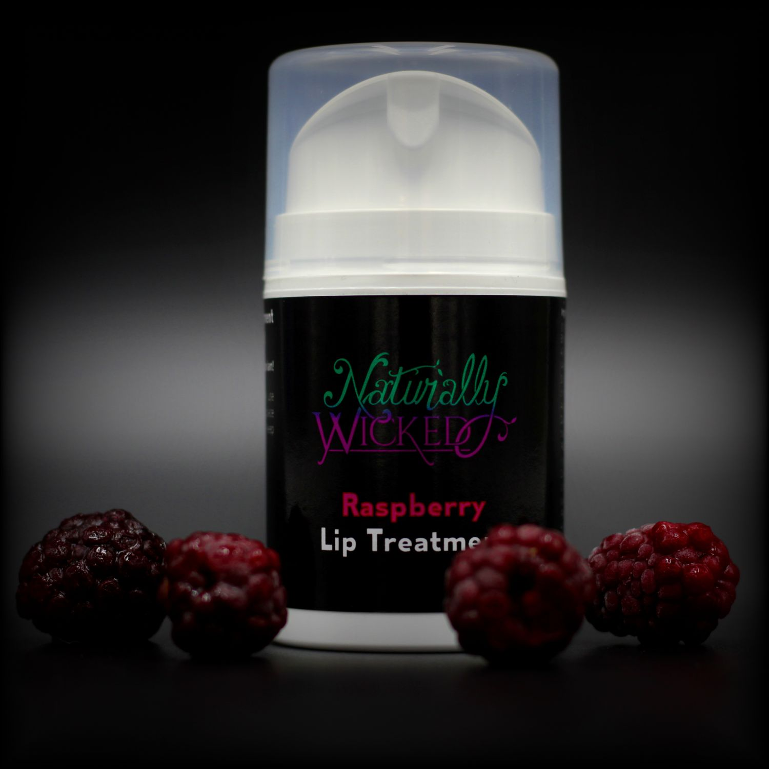 Naturally Wicked Raspberry Lip Treatment Surrounded By Dark Red Luscious Raspberries