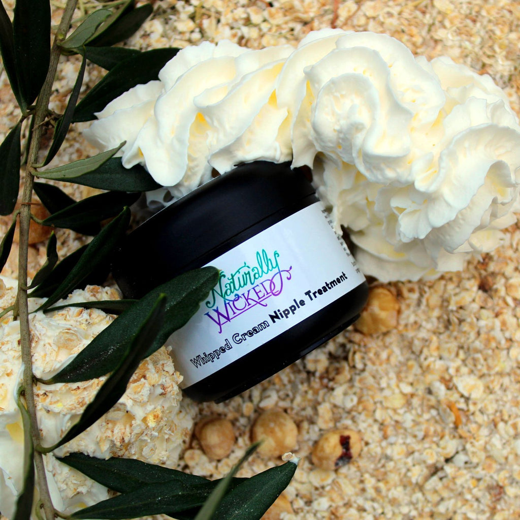Naturally Wicked Whipped Cream Nipple Treatment Surrounded By Natural Ingredients; Green Olive Leaves & Lay On A Bed Of Oats & Nuts