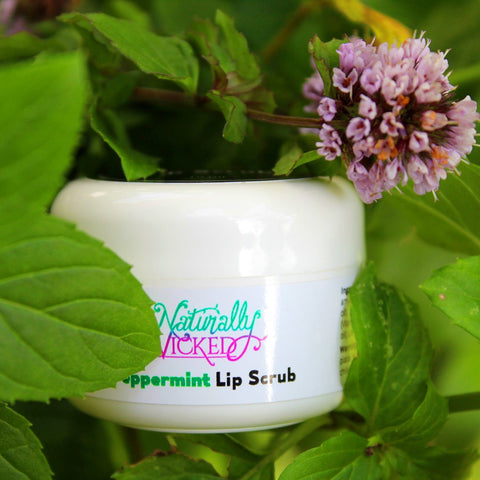 Naturally Wicked Peppermint Lip Scrub Surrounded By Bright Green Peppermint Leaves & Light Purple Mint Flower