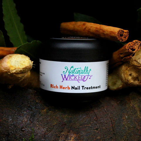 Naturally Wicked Rich Herb Nail Treatment On Brown Tree Root Surrounded By Ginger, Cinnamon & Camphor With Dark Hole Behind