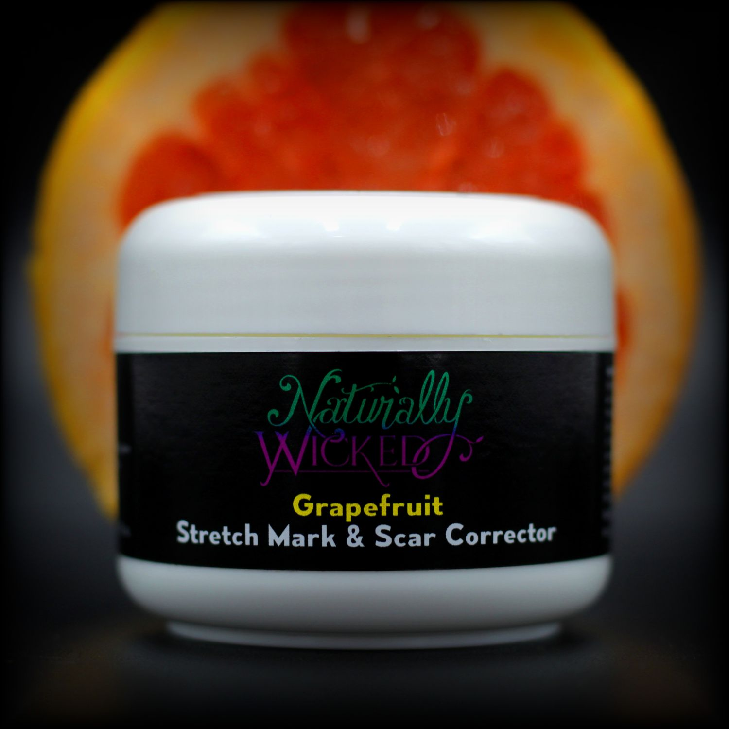 Naturally Wicked Grapefruit Stretch Mark & Scar Corrector In Front Of Red Sliced Grapefruit
